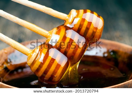 dipped in honey specially made from wood, a homemade rough spoon, sweet bee honey and three wooden spoons that allow you to transfer and pour honey without dripping and spreading