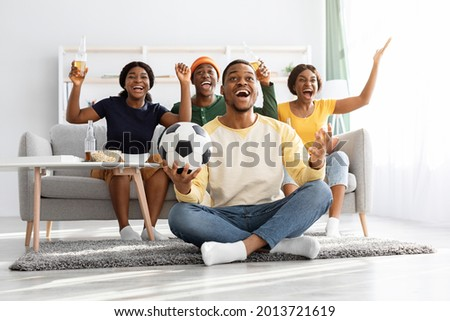 Emotional football fans young african american men and women watching game together at home, celebrating win of their team, raising hands up and screaming, excited black guy with soccer ball Royalty-Free Stock Photo #2013721619
