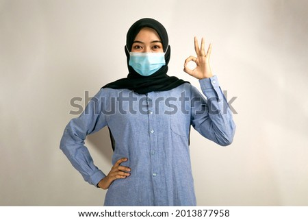 Muslim woman wearing medical mask, with ok sign hand, success sign, good work sign, victory sign, concept of preventing covid-19, concept of preventing corona virus, isolated on gray background