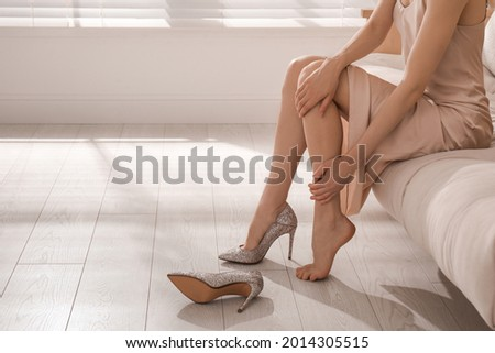 Young woman taking off shoes at home, closeup. Tired feet after wearing high heels Royalty-Free Stock Photo #2014305515