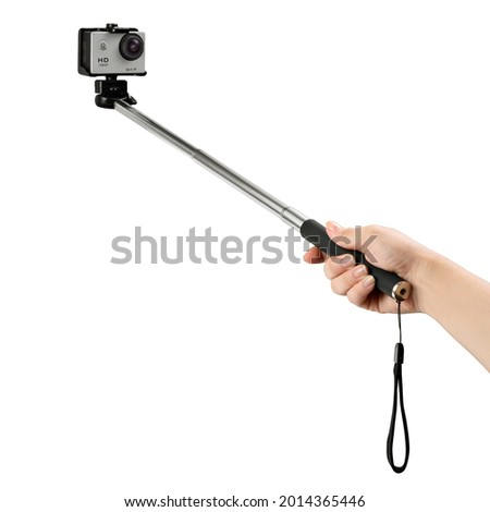 Female hand holding a selfie stick with a silver action cam on the tip on white background