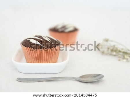 tasty chocolate cupcakes on white tablecloth