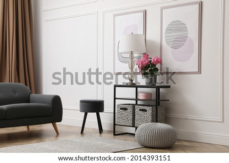 Console table with beautiful hydrangea flower and lamp near white wall in room. Interior design