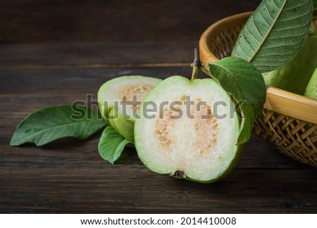 Ripe guava cut in half, four green leaves on an old wooden board. Royalty-Free Stock Photo #2014410008