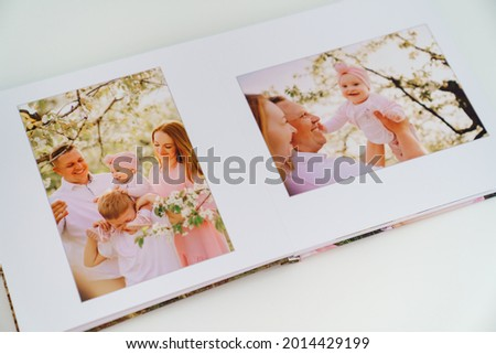 on white background open a photobook from a family photo shoot in the spring garden. Tradition print photo album and review and remember moments of life. services of photographer and designer. Royalty-Free Stock Photo #2014429199