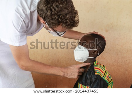 In this image a caucasian doctor in a white lab coat is checking out the throat of an aching black schoolboy with swollen lymph nodes as a possible symptom of corona virus infection. Royalty-Free Stock Photo #2014437455
