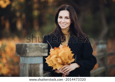 Picture of attractive woman goes for a walk in autumn park and holds a bouqet of yellow leaves