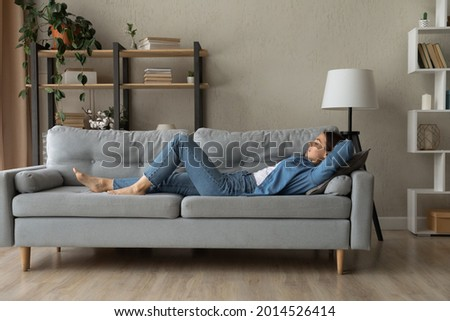 Side view woman enjoy day nap on comfy sofa. Young caucasian female put hands behind hear lying on cushion on cozy couch breath fresh conditioned air inside modern living room. Leisure, repose concept Royalty-Free Stock Photo #2014526414
