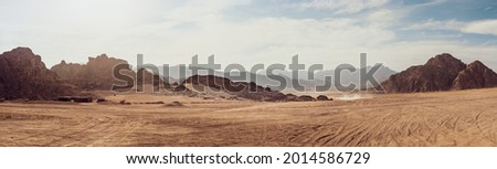 Safari and travel to Africa, extreme adventures or science expedition in a stone desert. Sahara desert at sunrise, mountain landscape with dust on skyline, hills and traces of the off-road car. Royalty-Free Stock Photo #2014586729