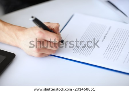 Young businessman signing document at table in white office close-up #201468851