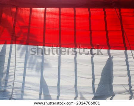 """this is a photo of the flag from Indonesia or in bahasa """"bendera merah putih"""" this photo is so unique because the reflection of shadows from trees and fences makes the flag seem unique"""