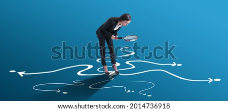 Choice and find your way concept with businesswoman looking through a magnifying glass on arrow roads drawn on bright blue surface Royalty-Free Stock Photo #2014736918