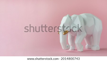An elephant figure on a pink background with an empty space for text. Cover, picture, advertising. The elephant is a symbol of intelligence, strength, wisdom