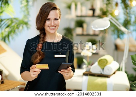 happy middle aged woman employee with smartphone and credit card browsing online shop in modern beauty studio.