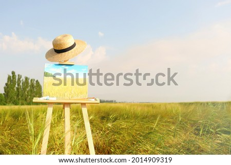 Wooden easel with beautiful picture, painting equipment and hat in field. Space for text
