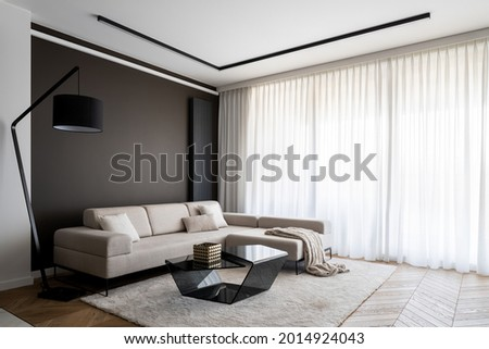 Bright and elegant living room with window wall behind curtains, stylish corner sofa and modern coffee table Royalty-Free Stock Photo #2014924043