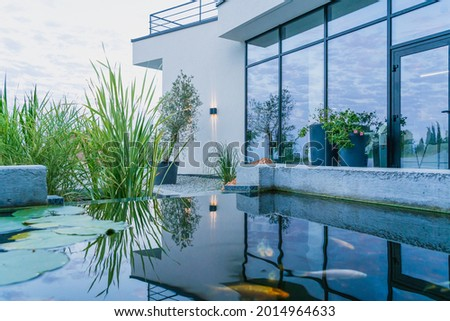 The water in the fish pond reflects the view of the glass wall of the modern home and creates a soothing mood. Out-of-town lifestyle Royalty-Free Stock Photo #2014964633