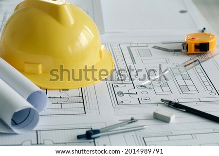 Yellow hard safety helmet hat and the blueprint, pen, ruler, protractor, and tape measure on the table at the construction site.for safety project of workman as engineer or worker, on city
