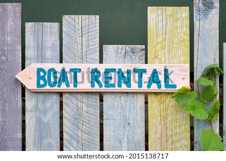 Sign with the inscription boat rental on a wooden fence on the river Spree in Berlin Kreuzberg in Germany