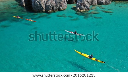 Aerial drone photo of women team of sport kayak in iconic beach and small cove of Tsigrado, Milos island, Cyclades, Greece