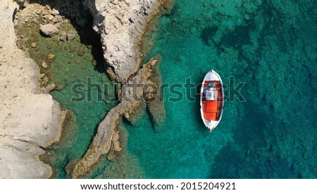 Aerial drone top down photo of traditional wooden fishing boat in iconic beach and small cove of Tsigrado, Milos island, Cyclades, Greece
