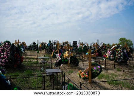 City cemetery with wooden crosses over the graves. Recent burials of people in the cemetery. Commemorative crosses with wreaths. Royalty-Free Stock Photo #2015330870