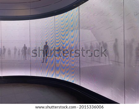 A curved led digital display screen wall. The wall is depicting moving shadows of people on a white background.  Royalty-Free Stock Photo #2015336006