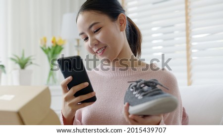 Young asia people happy teen girl smile unbox open gift new shoe buy order from online store shop take photo shoot camera show post social media app blog vlog share sit relax at home sofa couch.