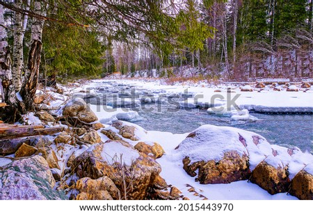 Rocky river bank in the snow. Winter forest river snow. Snowy river in winter forest. Winter forest river snow Royalty-Free Stock Photo #2015443970