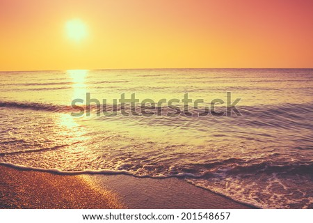 Soft Sea Ocean Waves Wash Over Golden Sand Background. Sunset, Sunrise, Sun. Toned like instant photo