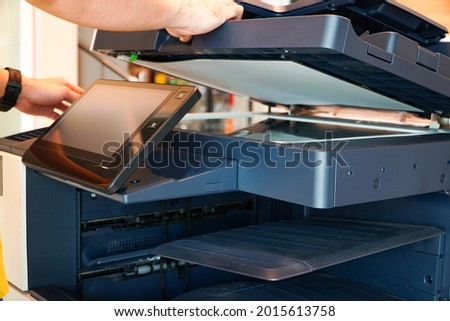 Men press the button of the copier. Man copying paper from Photocopier. Men use printing machines. man using photocopier  Royalty-Free Stock Photo #2015613758
