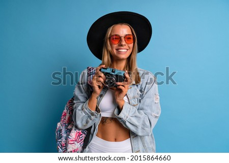 Studio portrait of cheerful stylish hipster photographer girl making pictures at old vintage film camera, wearing crop top denim jacket fedora hat and sunglasses, blue background.