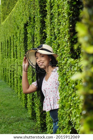 A picture of a beautiful Asian woman wearing a hat in her right hand holding a hat smiling in a banyan tree garden.