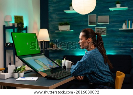 Photography designer working on retouching photo with green screen on display. Professional woman using mockup template and isolated chroma key on graphic software in editing studio