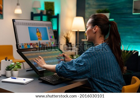 Photo editor artist doing touchpad work on retouching image using stylus and monitor screen for editing design on digital computer. Photographer woman working at production workplace