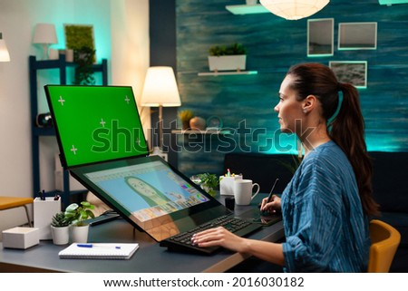 Woman photographer doing retouching work at studio with green screen, display chroma key for mockup template and isolated background. Colour professional editing photo for project