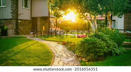 Beautiful manicured lawn and flowerbed with deciduous shrubs on private plot and track to house against backlit bright warm sunset evening light on background. Soft focusing in foreground. Royalty-Free Stock Photo #2016056351