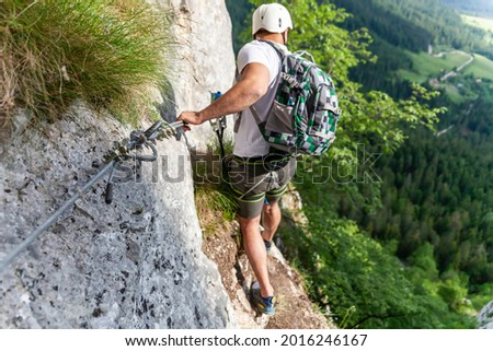 A young male climber on Via Ferati on beautiful European rocks Royalty-Free Stock Photo #2016246167