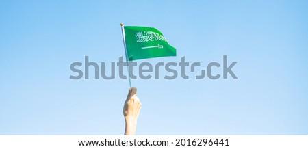 hand holding Saudi Arabia flag on blue sky background. September Saudi Arabia national day and Happy celebration concepts Royalty-Free Stock Photo #2016296441