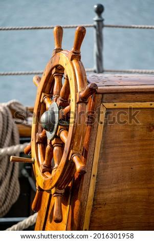 wooden ship's wheel of a tall ship Royalty-Free Stock Photo #2016301958