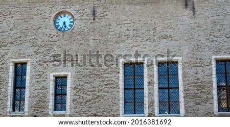 Facade of an old building with windows and an old clock. High quality photo