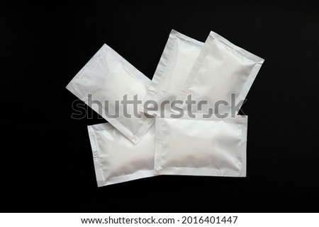 Blank white sachet packets stack mockup isolated on black background. Empty airtight pack mock-up for sauce, coffee, wet wipe, mayonnaise. Royalty-Free Stock Photo #2016401447