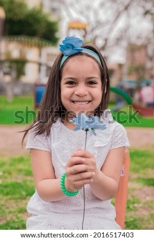 girl in dress sitting in a park with a flower in hand Royalty-Free Stock Photo #2016517403