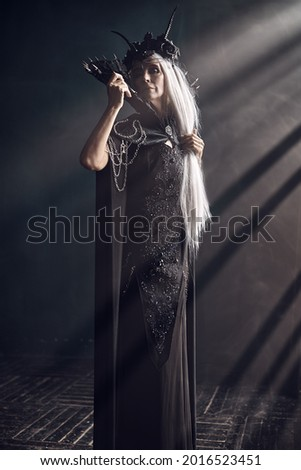A beautiful majestic black queen, a witch in a rich headdress and a rich black dress, stands in the rays of light in a dark castle. Fantasy World.  Royalty-Free Stock Photo #2016523451