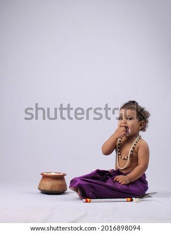Adorable Indian kid dressed up as little krishna  Shrikrishna or kanha kanhaiya on fancy dress Gokulashtami festival. eating curd butter Royalty-Free Stock Photo #2016898094