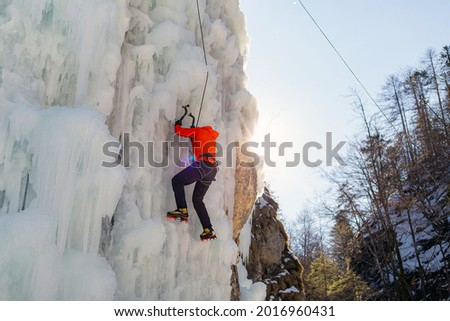 Aerial shot of a frozen ice waterfall, and the male climber progresses up the slope, while rope attached to his harness prevents him from falling Royalty-Free Stock Photo #2016960431