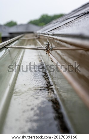 Selective focus on a section of residential guttering with hanger conveying water during a storm. Rain splatters and drops visible. Royalty-Free Stock Photo #2017039160