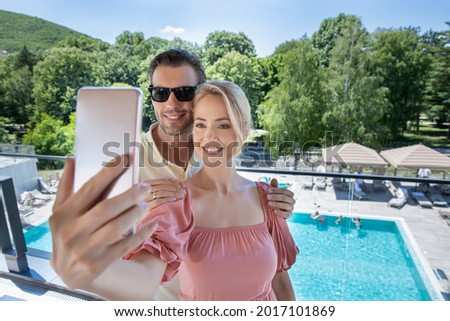 Handsome couple taking selfie with smartphone on a hotel swimming pool