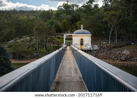 Mundaring Weir reservoir in the Darling Ranges, Perth, Western Australia. Pump house and walkway across the dam wall with forest landscape in the background Royalty-Free Stock Photo #2017117169