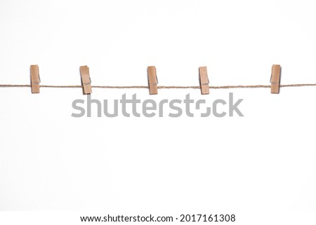 wooden clothespins on a rope on a white background, mock-up for design, copy space, rustic vintage style, clothesline for drying clothes with clothespins Royalty-Free Stock Photo #2017161308